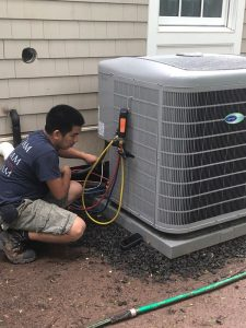 A Katham Industries Service Technician Works on a Carrier Air Conditioner